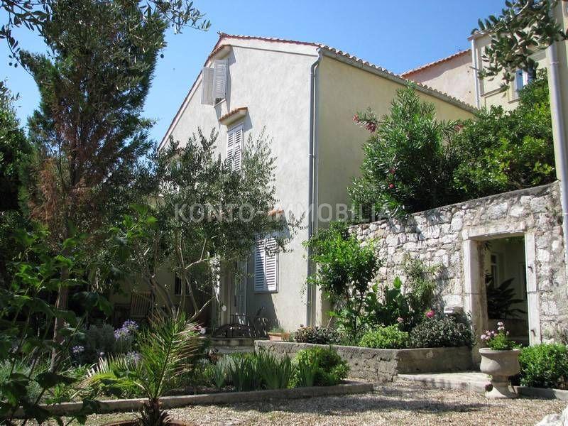 Kuća s dvorišnim prostorom omeđenim kamenim zidom, terasom i vrtom